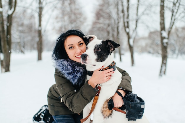 Young girl hugging her dog in winter park.