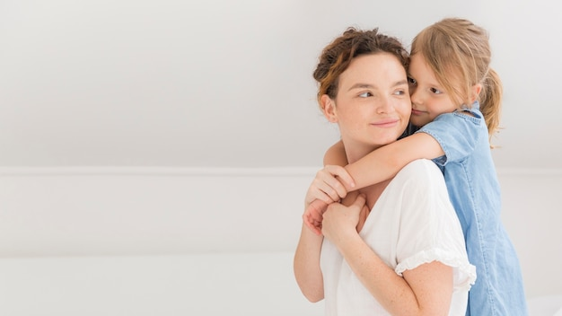 Ragazza che abbraccia la sua mamma a casa