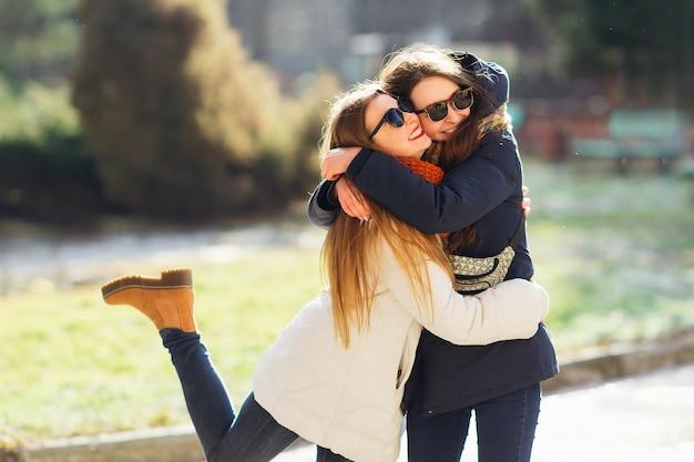 Молодая девушка обнимает ее старшую сестру улыбается.