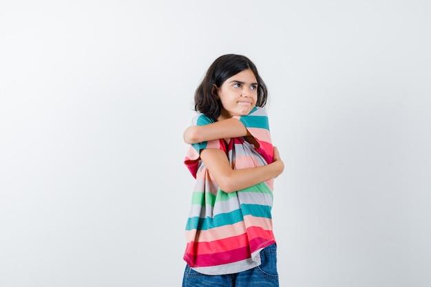 カラフルなストライプのtシャツで目をそらし、真剣に見える若い女の子。正面図。