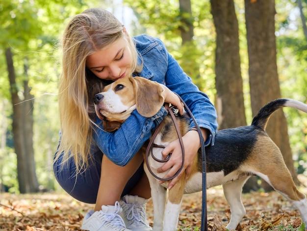 若い女の子が秋の公園でビーグル犬を抱きしめます