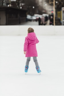 Young girl ice skating back shot