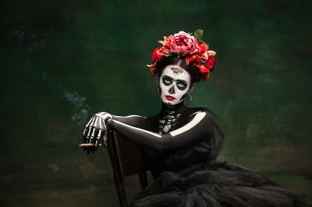 Young girl in the image of santa muerte saint death or sugar skull with bright makeup portrait
