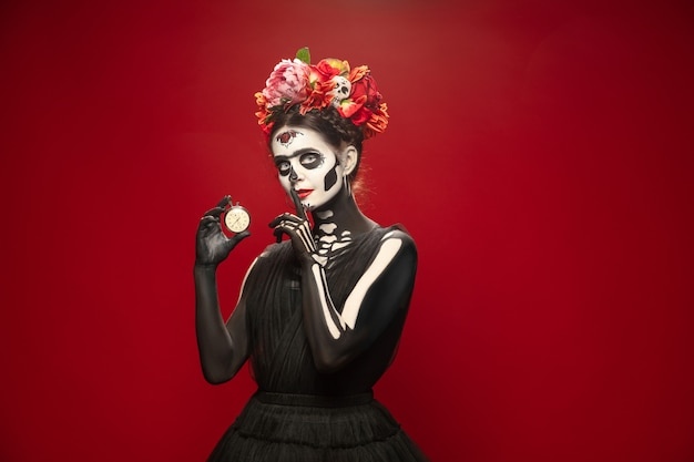 Young girl in the image of santa muerte, saint death or sugar skull