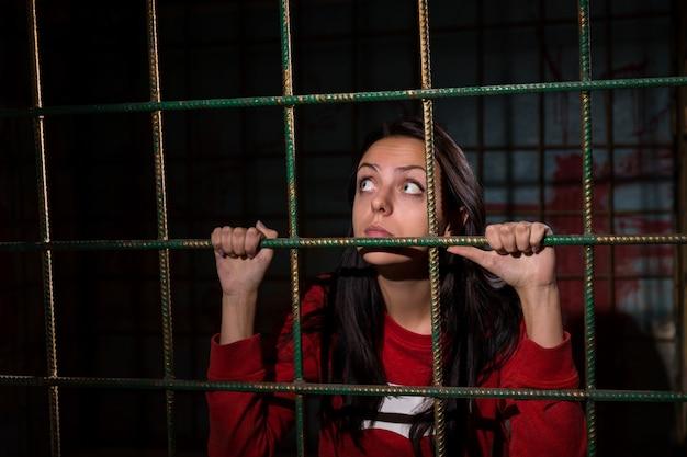 運命を待っている恐怖に座っている彼女の後ろに血が飛び散った壁で金属の檻に投獄された少女