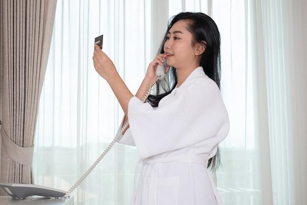 Молодая девушка в халате в халате держит кредитную карту во время разговора
