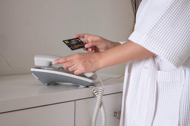 Молодая девушка в халате в халате с кредитной картой