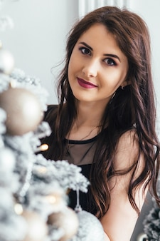 Young girl in a black dress poses before a shiny Christmas tree