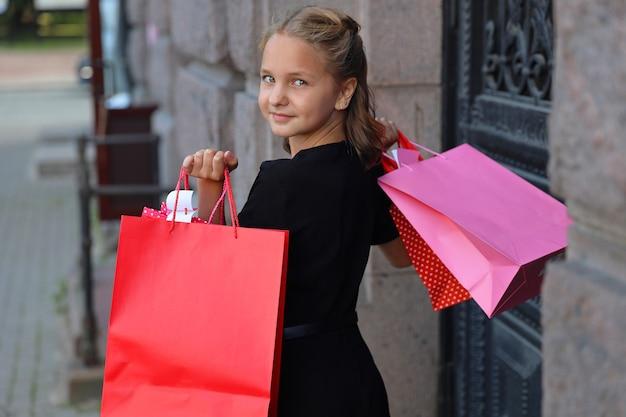 色付きのバッグと黒のドレスを着た少女