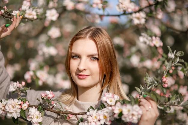Молодая девушка в цветущем яблоневом саду