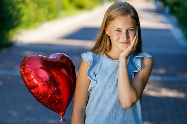 ハート型の風船と青いドレスを着た若い女の子