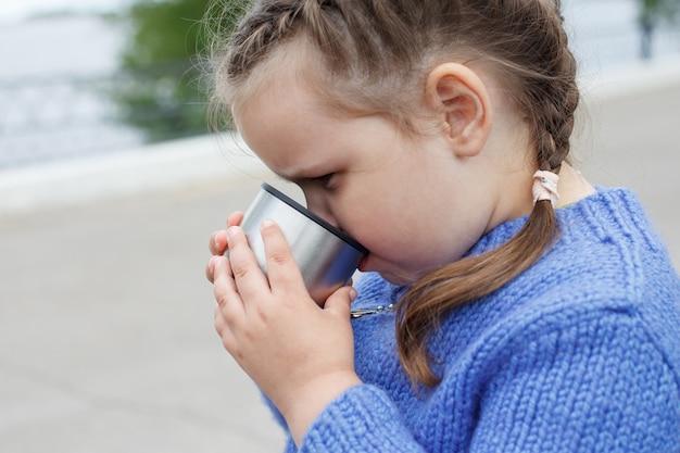 青いニットセーターの少女は、魔法瓶カップから屋外でお茶やコーヒーを飲みます。