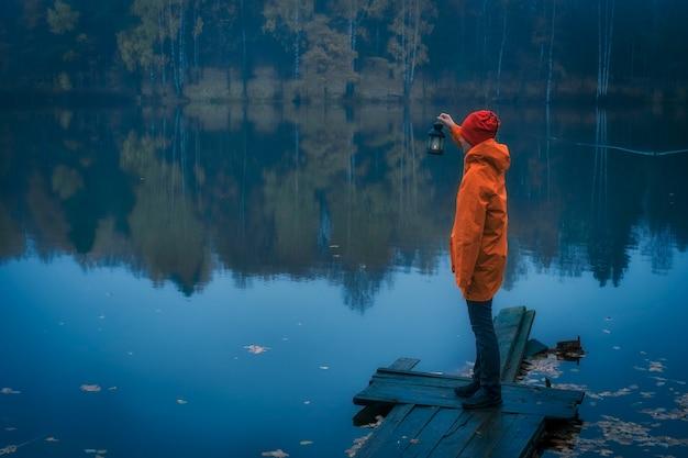 Молодая девушка в ярко-желтом плаще с фонариком ищет что-то в тумане на озере
