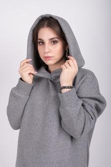 Молодая девушка в серой кофте с капюшоном на голове.
