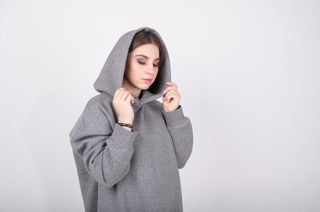彼女の頭にフード付きの灰色のスウェットシャツの少女。