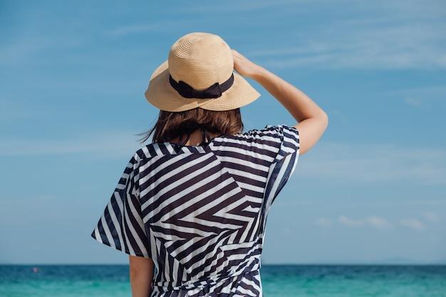Молодая девушка в шляпе в полосатом платье на пляже. таиланд, бамбуковый остров