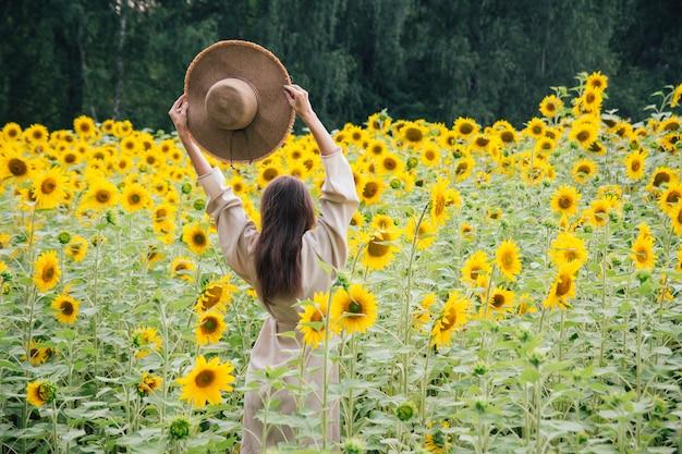Молодая девушка в шляпе на поле подсолнухов