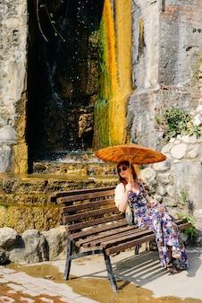 Молодая девушка в длинном платье сидит на деревянной скамейке с китайским зонтиком