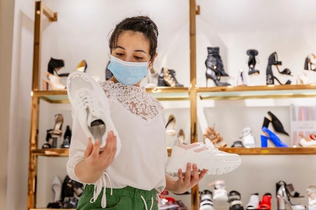 의료 마스크에 어린 소녀는 신발이 게에서 신발을 선택합니다. 쇼핑 및 엔터테인먼트. 코로나 바이러스 전염병 예방 조치.