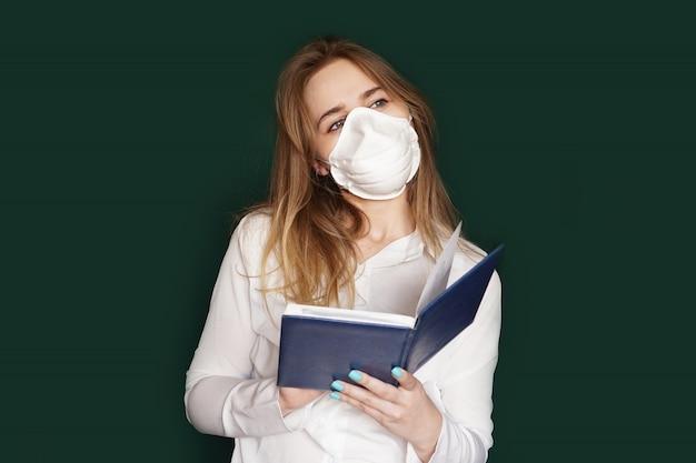 手にノートを持つ医療マスクの少女