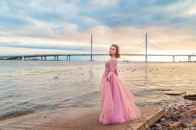 Молодая девушка в розовом платье танцует на берегу моря. беззаботность, свобода, молодость. летний вечер.