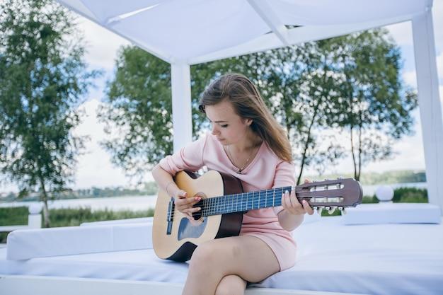 Молодая девушка в розовое платье, играя на гитаре