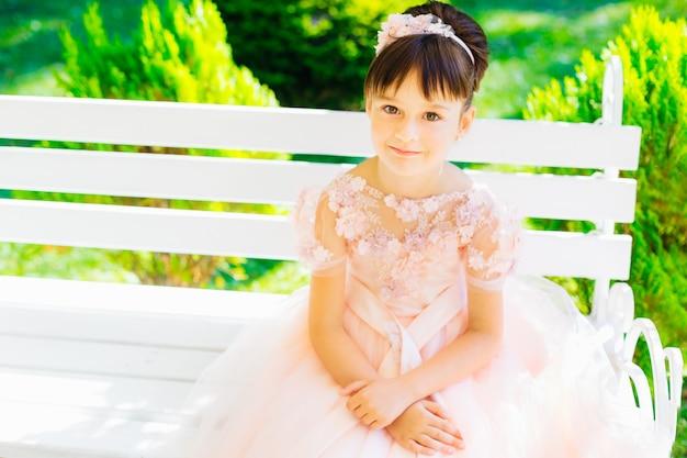 녹색 숲의 표면에 흰색 벤치에 앉아 핑크 드레스에 어린 소녀