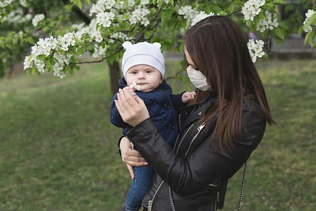 보호 마스크에 어린 소녀는 그녀의 어린 아이를 안 아