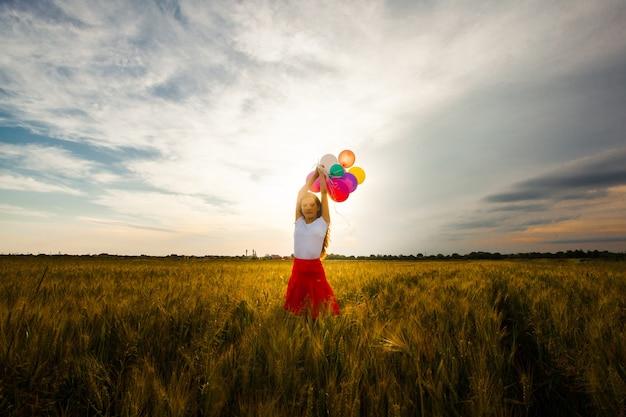 麦畑で色の風船で走っている赤いスカートの少女。自然のインスピレーション、バックライト