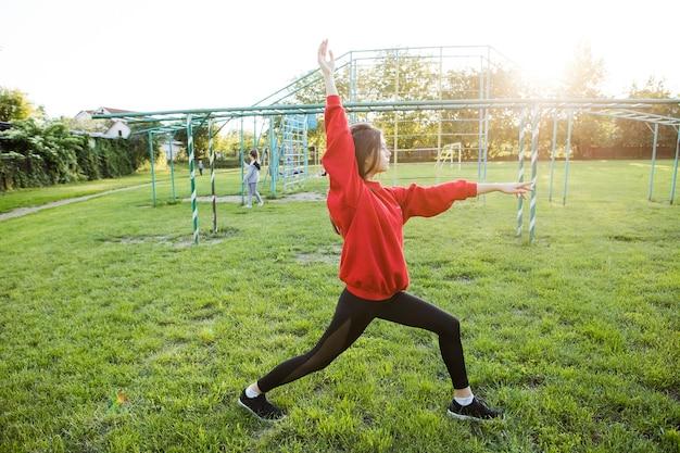 Молодая девушка в красной спортивной куртке занимается спортом на стадионе