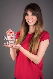 Молодая девушка в красной футболке с тележкой для покупок