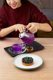 Молодая девушка в ресторане за столом с черничным тортом и тайским синим чаем, подается с медом и черничным пирогом на деревянном столе