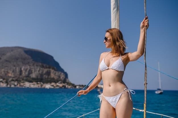Молодая девушка в купальнике на роскошной яхте.