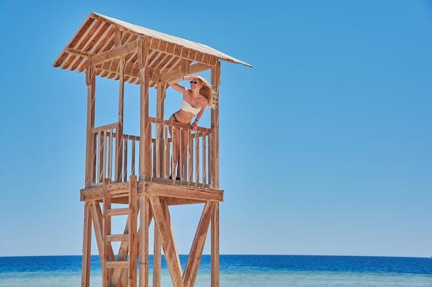 ビーチのライフガードタワーで水着姿の少女