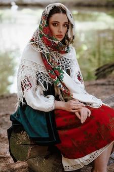 Молодая девушка в традиционной вышитой одежде сидит на скамейке у озера