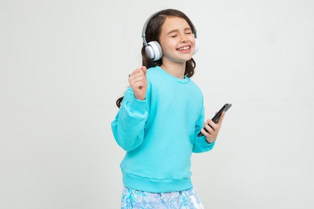 Молодая девушка в бирюзовой блузке наслаждается музыкой с наушниками, держа телефон против студии с копией пространства