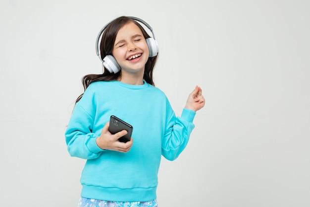 Молодая девушка в бирюзовой блузке слушает музыку в наушниках, держа телефон на студии с копией пространства