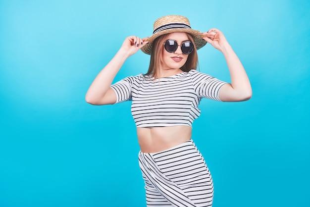 흰색과 검은 색 줄무늬, 모자, 선글라스에 어린 소녀, 완벽한 몸매를 가진 밝은 파란색 배경에 감정적으로 열린 입. 외딴. 스튜디오 촬영.