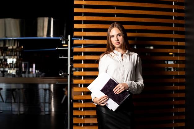 그녀의 손에 노트북과 서류와 흰 셔츠와 검은 치마에 어린 소녀