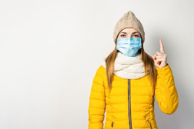 黄色のジャケットと彼女の顔に医療マスクを持つ帽子の少女は彼女の指を保持