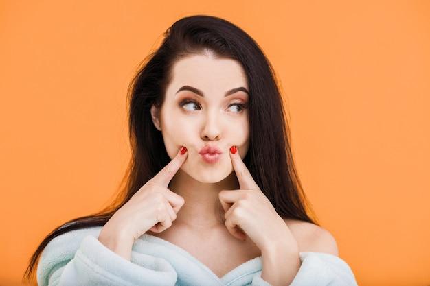Молодая девушка в халате с голыми плечами позирует на оранжевом фоне