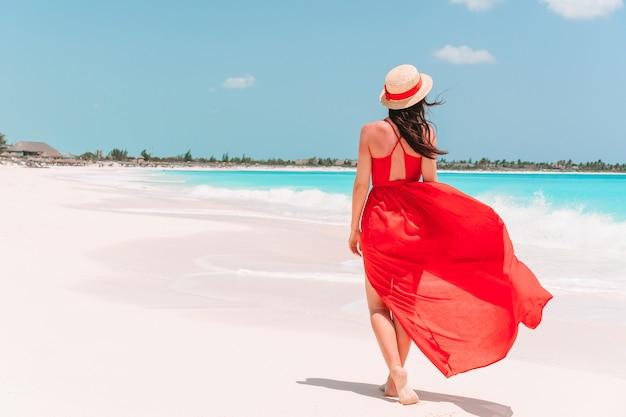 Молодая девушка в красивом красном платье на пляже