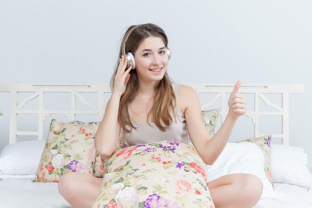 音楽のヘッドフォンを聞いてベッドの中で若い女の子