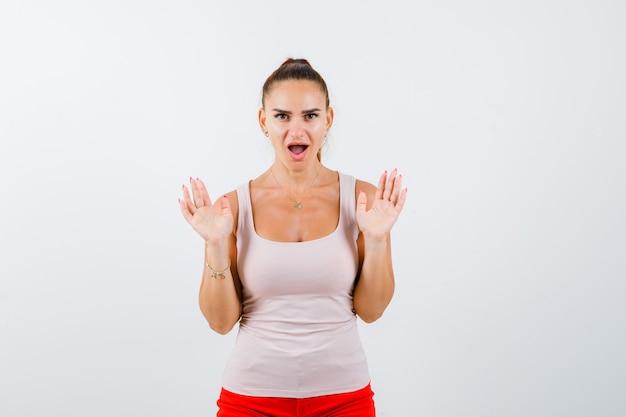 베이지 색 상단과 빨간색 바지에 어린 소녀 항복 제스처에 손바닥을 제기하고 놀란, 전면보기를보고.