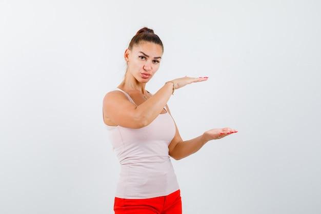 Молодая девушка в бежевом топе и красных штанах показывает весы и выглядит серьезным, вид спереди.