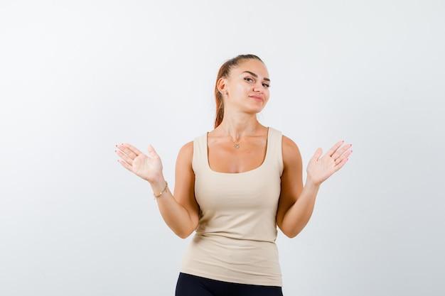 ベージュのトップの若い女の子、脇に手のひらを広げてきれいに見える黒いズボン、正面図。