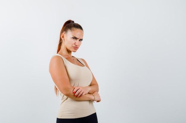 ベージュのトップの若い女の子、腕を組んで立っている黒いズボン、肩越しに見て、自信を持って、正面図。