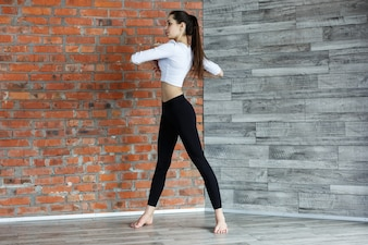 Young girl in black and white clothes does warming up before a work-out in gym