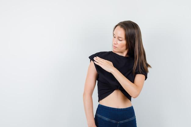 Молодая девушка в черной блузке, штанах демонстрирует превосходство, вытирая плечо, и выглядит скрупулезно