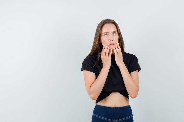 Молодая девушка в черной блузке, штаны опускают щеки и выглядят раздраженными